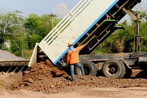 Dump truck unloading dirt.