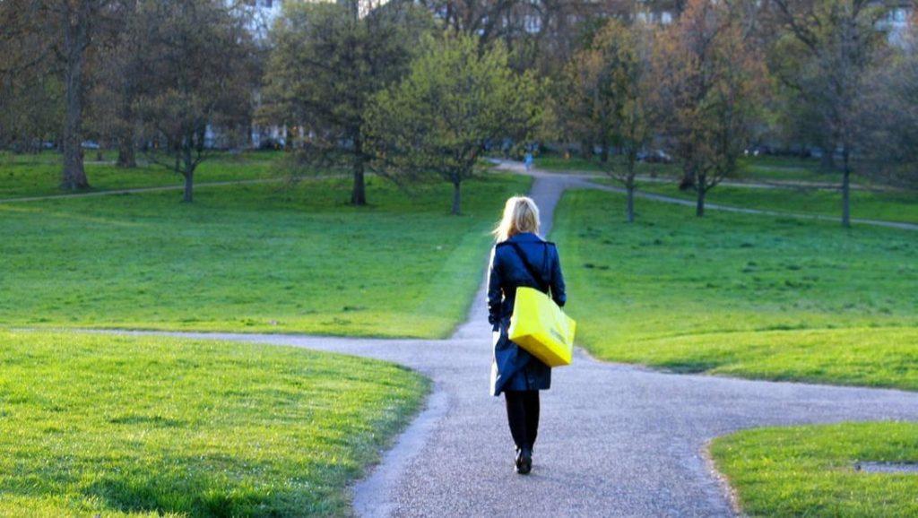 A woman walking through a park comes to a crossroads.