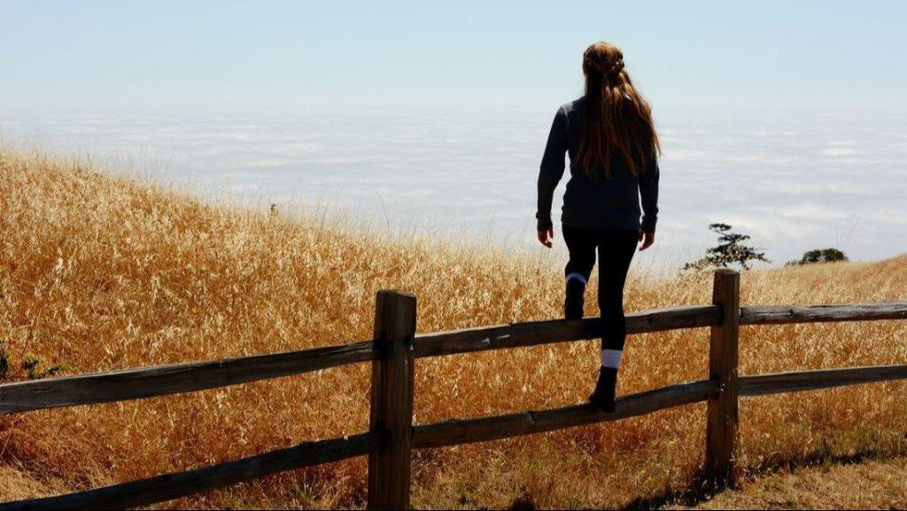 A woman climbing over a fence.