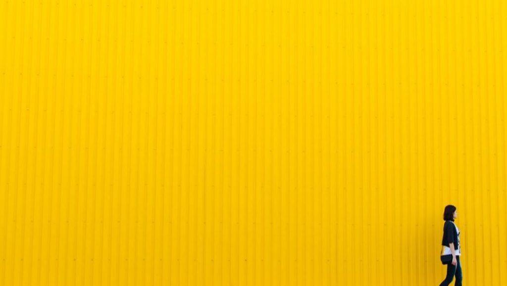 A woman walking along a bright yellow, corrugated wall.